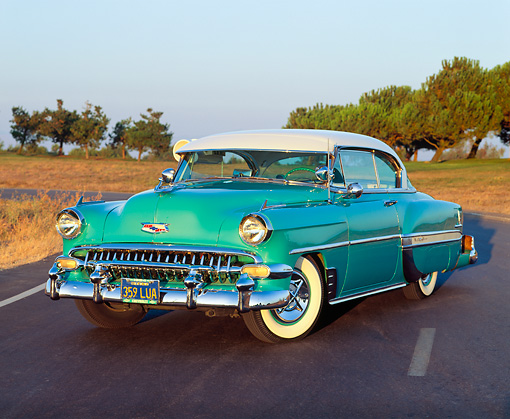AUT 21 RK0753 02 © Kimball Stock 1954 Chevrolet Bel Air Turquoise 3/4 Front View On Road Dry Grass And Trees At Dusk