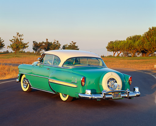 AUT 21 RK0754 04 © Kimball Stock 1954 Chevrolet Bel Air Turquoise And White 3/4 Rear View On Pavement At Dusk Trees