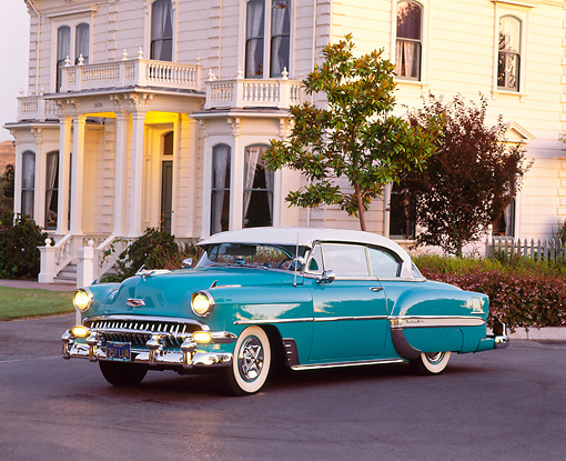 AUT 21 RK0760 02 © Kimball Stock 1954 Chevrolet Bel Air Turquoise And White 3/4 Side View On Pavement By House