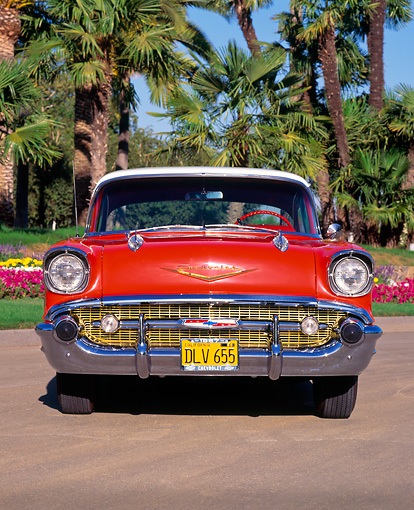 AUT 21 RK0773 02 © Kimball Stock 1957 Chevy Bel Air Sport Coupe Red Head On Shot On Pavement By Palm Trees And Flowers Blue Sky