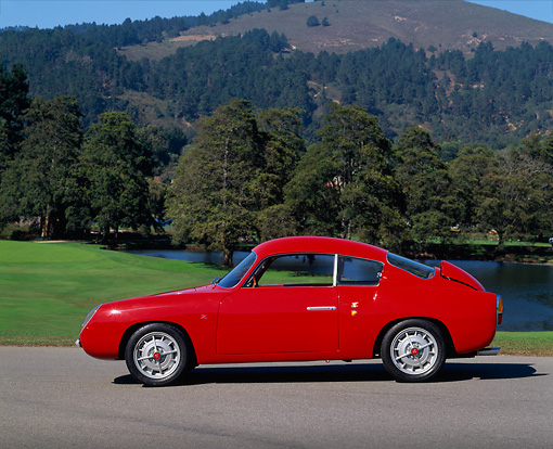 AUT 21 RK0788 01 © Kimball Stock 1959 Abarth Zagato Double Bubble Coupe Red Side View On Pavement Grass And Trees Background