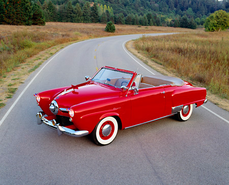 AUT 21 RK0814 07 © Kimball Stock 1950 Studebaker Convertible Red Overhead 3/4 Side View On Road Headlights On By Dry Grass And Trees