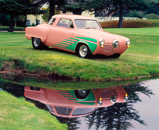AUT 21 RK0827 01 © Kimball Stock 1951 Studebaker Pro Street Peach And Green 3/4 Side View On Grass Hill By Water Parking Lights On