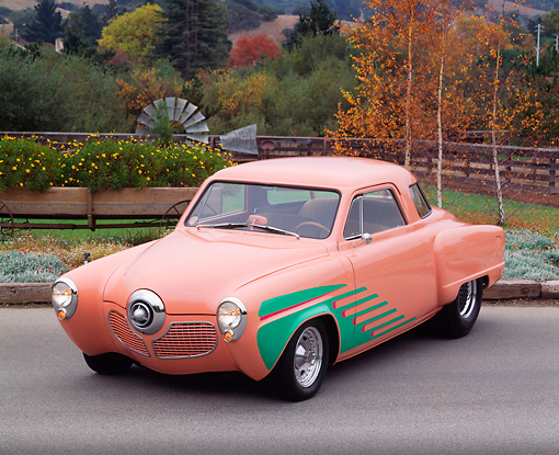 AUT 21 RK0832 04 © Kimball Stock 1951 Studebaker Street Rod Peach And Green 3/4 Front View On Pavement By Trees And Flowers Headlights On