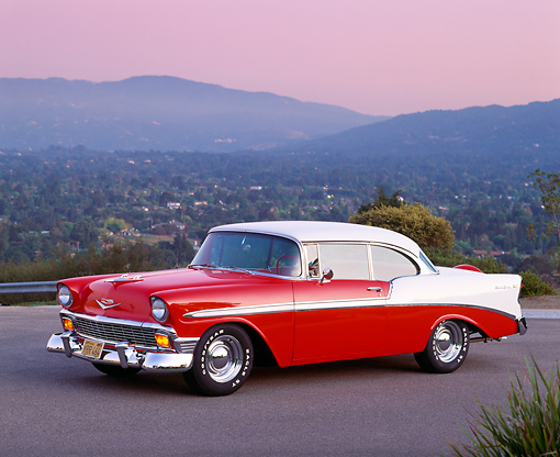 AUT 21 RK0839 09 © Kimball Stock 1956 Chevy Bel Air Red And White 3/4 Side View On Pavement Mountains Background At Dusk