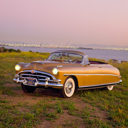 AUT 21 RK0852 02 © Kimball Stock 1953 Hudson Hornet Convertible Gold 3/4 Front View On Dirt Headlights On By Water At Dusk