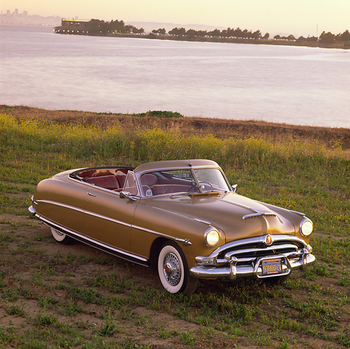 AUT 21 RK0853 05 © Kimball Stock 1953 Hudson Hornet Convertible Gold Overhead Front 3/4 View On Dirt Headlights On By Water