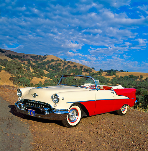 AUT 21 RK0876 02 © Kimball Stock 1955 Olds Super 88 Red And White Convertible 3/4 Side View On Dirt Hills Cloudy Blue Sky