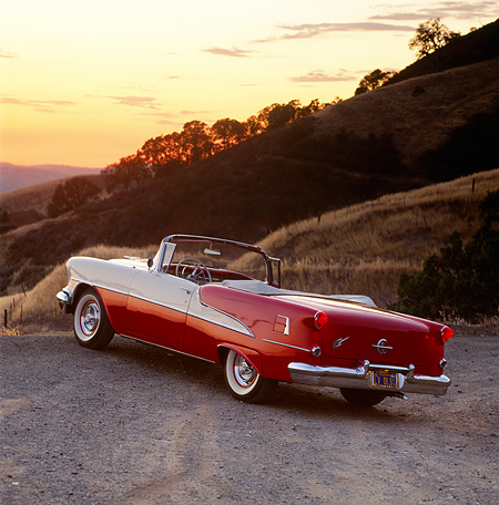 AUT 21 RK0880 03 © Kimball Stock 1955 Olds Super 88 Red And White Convertible 3/4 Rear View On Dirt By Hill Orange Sky At Dusk