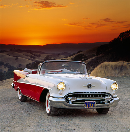 AUT 21 RK0883 07 © Kimball Stock 1955 Oldsmobile Super 88 Red And White Convertible 3/4 Front View On Gravel Sunset Background Orange Sky