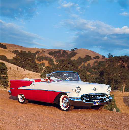 AUT 21 RK0884 02 © Kimball Stock 1955 Oldsmobile Super 88 Red And White 3/4 Side View On Dirt By Hills Cloudy Blue Sky