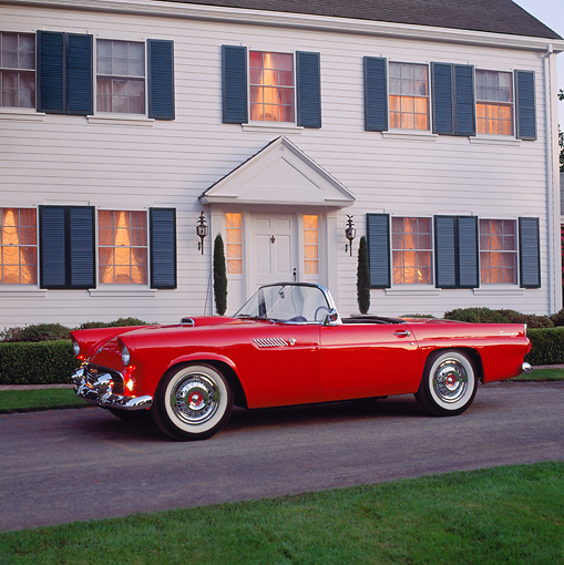 AUT 21 RK0889 03 © Kimball Stock 1955 Ford Thunderbird Red Side 3/4 View On Pavement In Front Of House Parking Lights On At Dusk