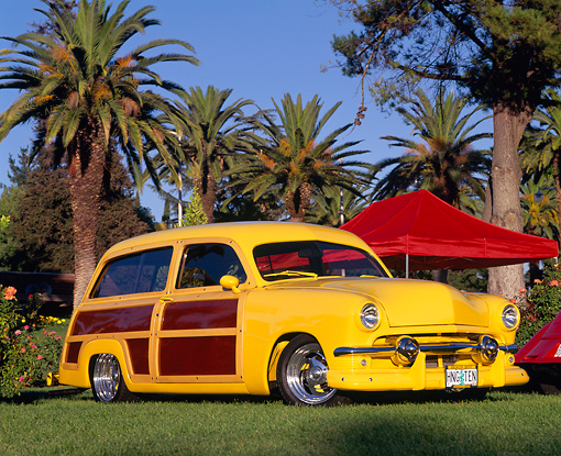 AUT 21 RK0901 01 © Kimball Stock 1951 Ford Woody Wagon Yellow Wood Panel Low 3/4 Side View On Grass Palm Trees Blue Sky