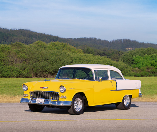 AUT 21 RK0910 10 © Kimball Stock 1955 Chevy 210 Sedan Yellow And White 3/4 Front View On Pavement By Trees And Grass Blue Sky