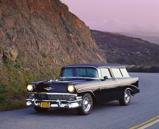 AUT 21 RK0921 02 © Kimball Stock 1956 Chevy Nomad Wagon Black 3/4 Front View On Road Headlights On Side Of Hill Purple Sky