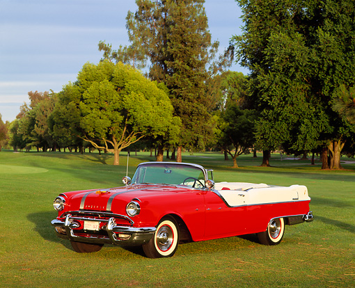 AUT 21 RK0954 08 © Kimball Stock 1955 Pontiac Star Chief Convertible Red And White Side 3/4 View On Grass By Trees