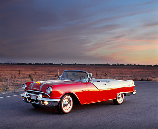AUT 21 RK0958 01 © Kimball Stock 1955 Pontiac Star Chief Convertible Red And White Side 3/4 View On Pavement Pink Clouds At Dusk