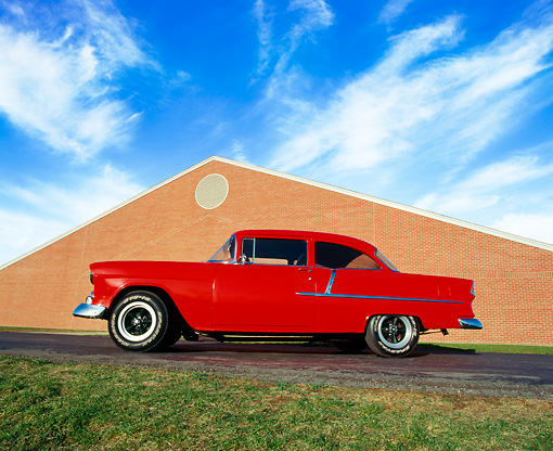 AUT 21 RK0984 02 © Kimball Stock 1955 Chevy 210 Custom Rod Red Low Profile View On Pavement By Brick Building Blue Sky