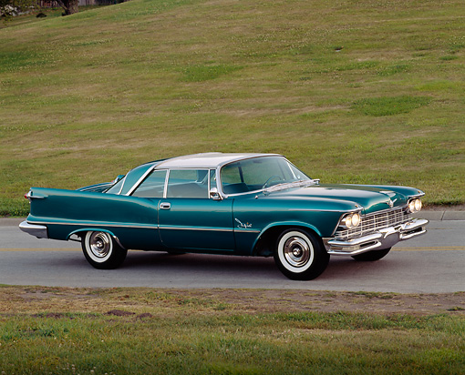AUT 21 RK0999 04 © Kimball Stock 1957 Chrysler Imperial Crown Coupe Teal 3/4 Side View On Road By Grass Hill