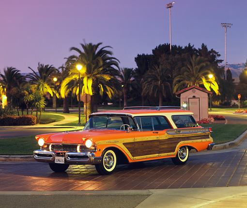 AUT 21 RK1026 04 © Kimball Stock 1957 Mercury Colony Park Station Wagon Orange 3/4 Side View Headlights On By Trees Purple Sky At Night