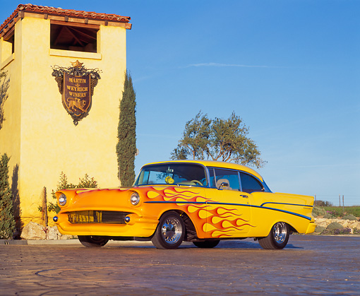 AUT 21 RK1047 11 © Kimball Stock 1957 Chevy Bel Air Custom Yellow With Flames Low 3/4 Side View By Building Trees Blue Sky