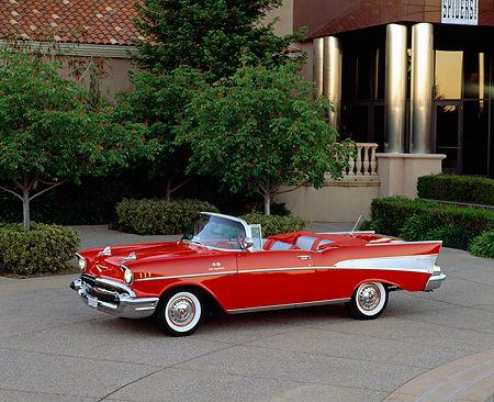 AUT 21 RK1057 06 © Kimball Stock 1957 Chevy Bel Air Convertible Fuel Injection Red 3/4 Side View On Pavement By Building And Trees