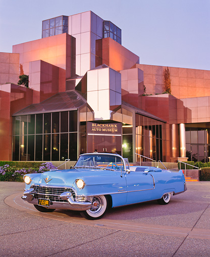 AUT 21 RK1072 01 © Kimball Stock 1955 Cadillac Convertible Blue 3/4 Front View On Pavement By Lighted Building At Dusk