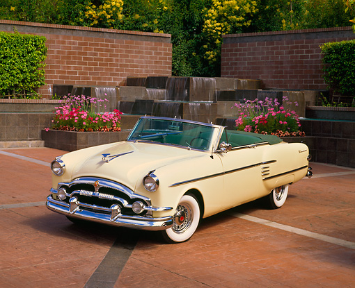 AUT 21 RK1079 02 © Kimball Stock 1954 Packard Convertible Yellow 3/4 Front View On Brick Pavement By Water Fountain
