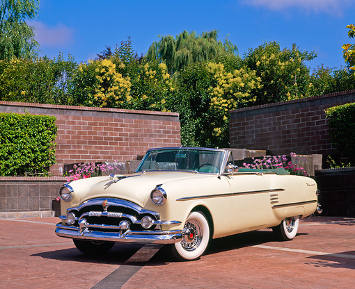 AUT 21 RK1080 06 © Kimball Stock 1954 Packard Convertible Yellow 3/4 Front View On Brick Pavement By Brick Wall And Fountain