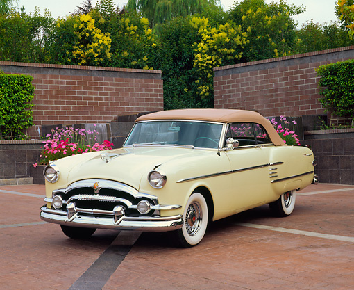 AUT 21 RK1081 02 © Kimball Stock 1954 Packard Convertible Yellow 3/4 Front View On Brick Pavement By Brick Wall Water Fountain