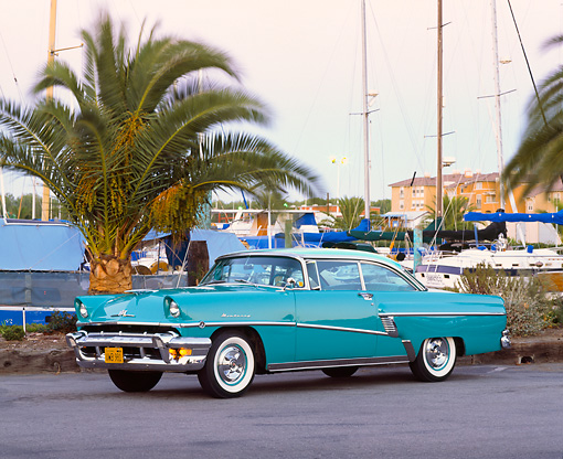 AUT 21 RK1086 01 © Kimball Stock 1956 Mercury Monterey Hardtop Green 3/4 Side View On Pavement By Boat Harbor