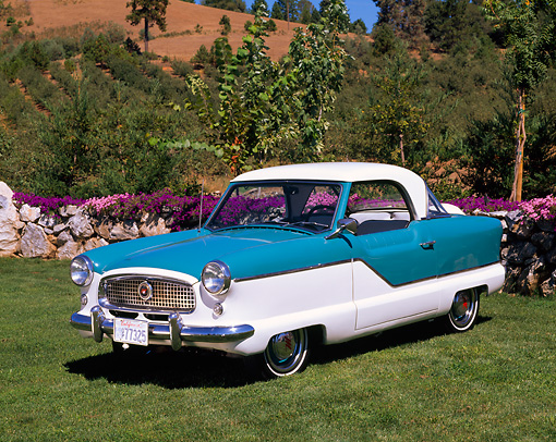 AUT 21 RK1141 01 © Kimball Stock 1958 Nash Metropolitan Blue And White 3/4 Side View On Grass By Trees