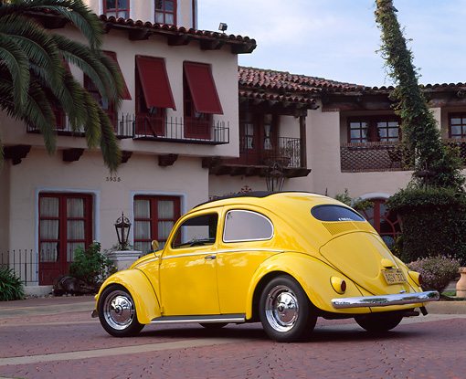 AUT 21 RK1191 05 © Kimball Stock 1956 Volkswagen Bug Rag Top Yellow Low 3/4 Rear View On Pavement By Spanish Building
