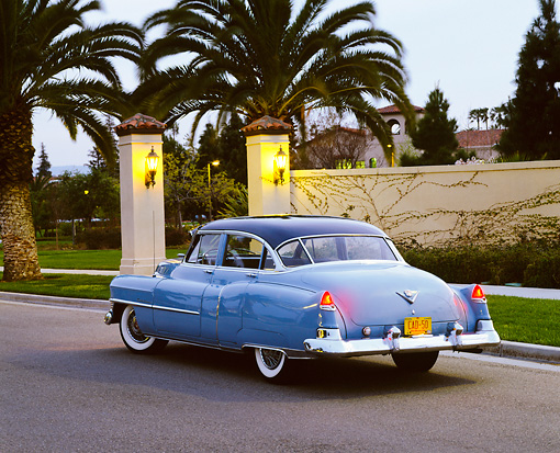 AUT 21 RK1257 01 © Kimball Stock 1950 Cadillac Blue 3/4 Rear View On Pavement By Wall And Palm Trees At Dusk