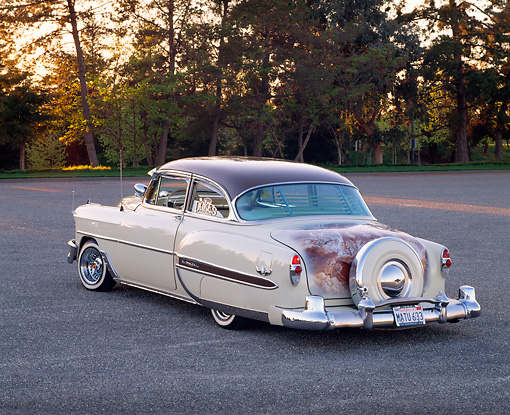 AUT 21 RK1258 03 © Kimball Stock 1953 Chevy Bel Air Lowrider Beige And Brown 3/4 Rear View On Pavement By Trees