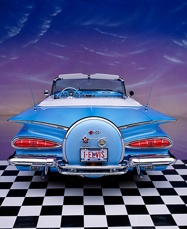 AUT 21 RK1272 09 © Kimball Stock 1959 Chevy Impala Lowrider Convertible Blue Rear Shot On Checkerboard Pink Clouds