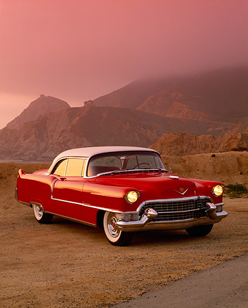AUT 21 RK1305 02 © Kimball Stock 1955 Cadillac Series 62 Coupe Red And White 3/4 Front View On Sand Rock Mountains Fog Red Filtered