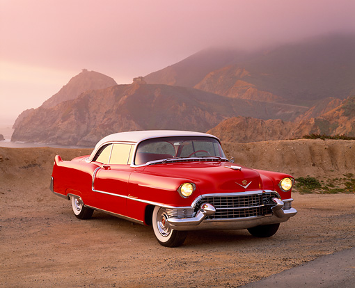 AUT 21 RK1305 14 © Kimball Stock 1955 Cadillac Series 62 Coupe Red And White 3/4 Front View On Sand Rock Mountains Fog Red Filtered