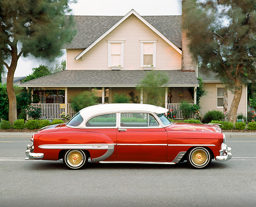 AUT 21 RK1311 05 © Kimball Stock 1953 Chevy Bel Air Lowrider Red Profile On Pavement By House At Dusk