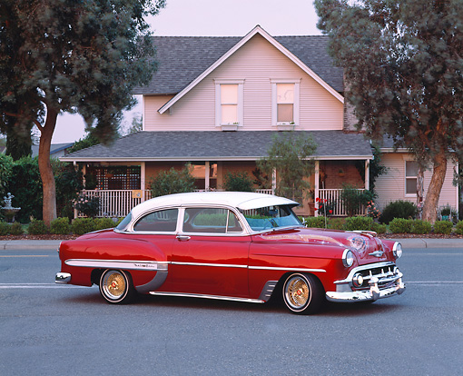 AUT 21 RK1312 04 © Kimball Stock 1953 Chevy Bel Air Lowrider Red 3/4 Side View On Pavement By House And Trees At Dusk