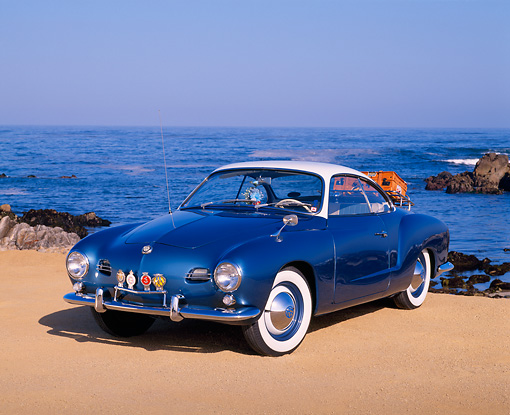 AUT 21 RK1376 02 © Kimball Stock 1959 Karmann Ghia Coupe Blue And White 3/4 Front View On Sand