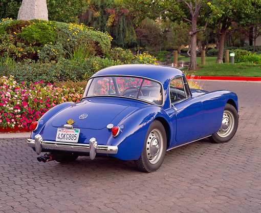 AUT 21 RK1467 03 © Kimball Stock 1958 MGA Coupe Blue 3/4 Rear View On Pavement By Flowers