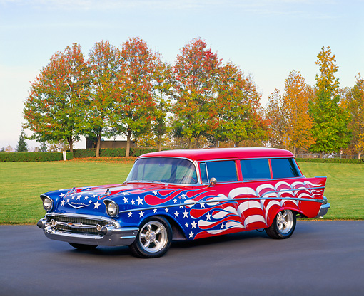 AUT 21 RK1468 02 © Kimball Stock 1957 Chevy 210 Wagon American Flag Graphics 3/4 Side View On Pavement By Grass Fall Trees