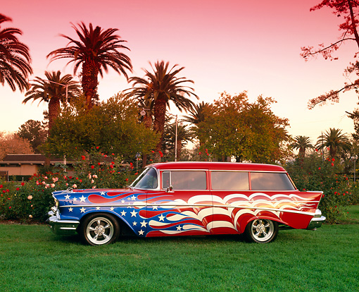AUT 21 RK1471 02 © Kimball Stock 1957 Chevy 210 Wagon American Flag Graphics Side View On Grass By Trees Pink Sky