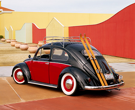 AUT 21 RK1491 07 © Kimball Stock 1955 VW Bug European Oval Window Roof Rack Red And Black 3/4 Rear View By Fence