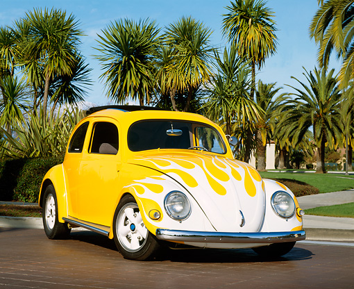 AUT 21 RK1492 04 © Kimball Stock 1956 Volkswagen Beetle  Yellow With Flames Low 3/4 Front View By Palm Trees