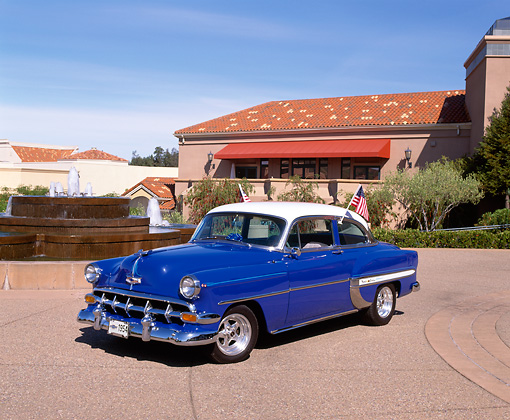 AUT 21 RK1536 03 © Kimball Stock 1954 Chevrolet Bel Air Blue White Top 3/4 Front View By Water Fountain