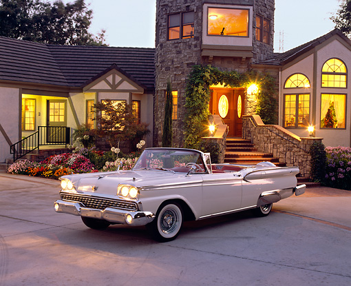 AUT 21 RK1538 01 © Kimball Stock 1959 Ford Fairlane 500 Retractable White 3/4 Front View By Lighted House At Dusk