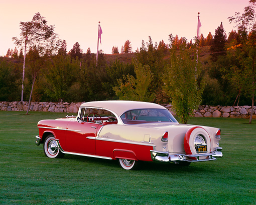 AUT 21 RK1560 05 © Kimball Stock 1955 Chevy Bel Air Red And W White 3/4 Rear View On Grass By Trees At Dusk