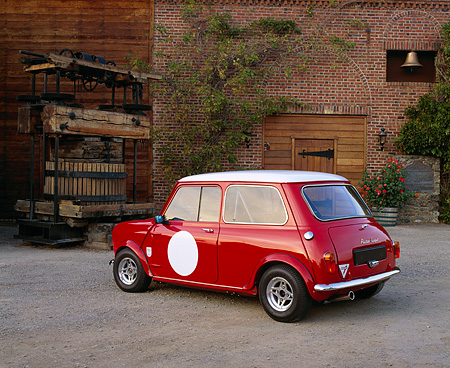 AUT 21 RK1597 04 © Kimball Stock 1959 Mini Cooper Red And White 3/4 Rear View On Gravel By Water Well By Brick Building